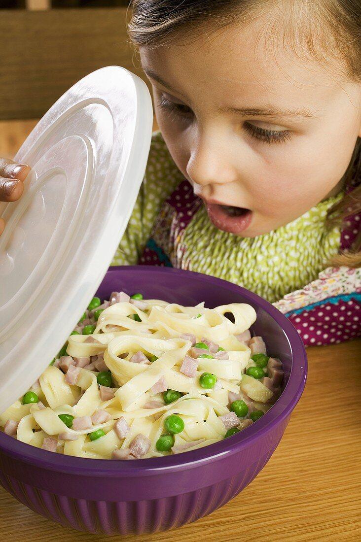 Surprised girl looking at pasta dish