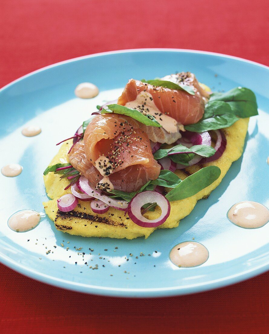 Gravlax with onions and chard leaves on polenta