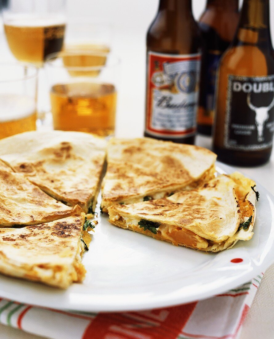 Sweet potato quesadilla on plate in front of beer bottles