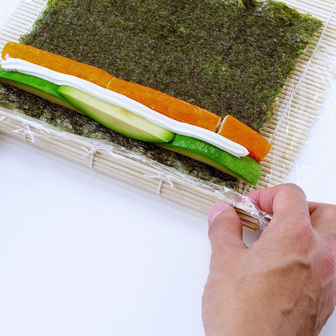 Making California rolls (rolling up bamboo mat)