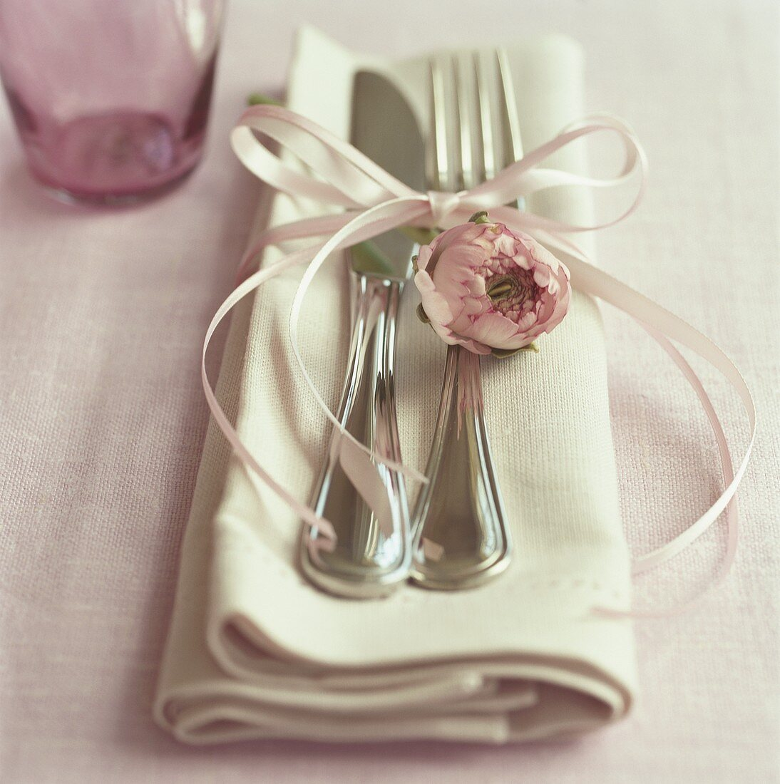 Silver cutlery with bow and pink flower on fabric napkin