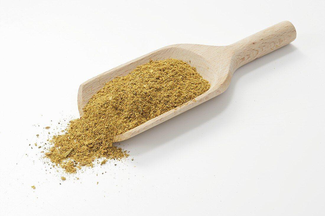 Raz el Hanout (Moroccan spice mixture) in wooden scoop