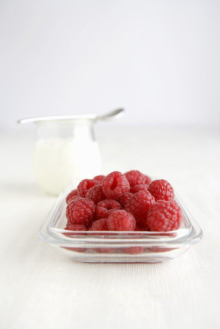 Fresh raspberries in glass dish, jar of yoghurt in background