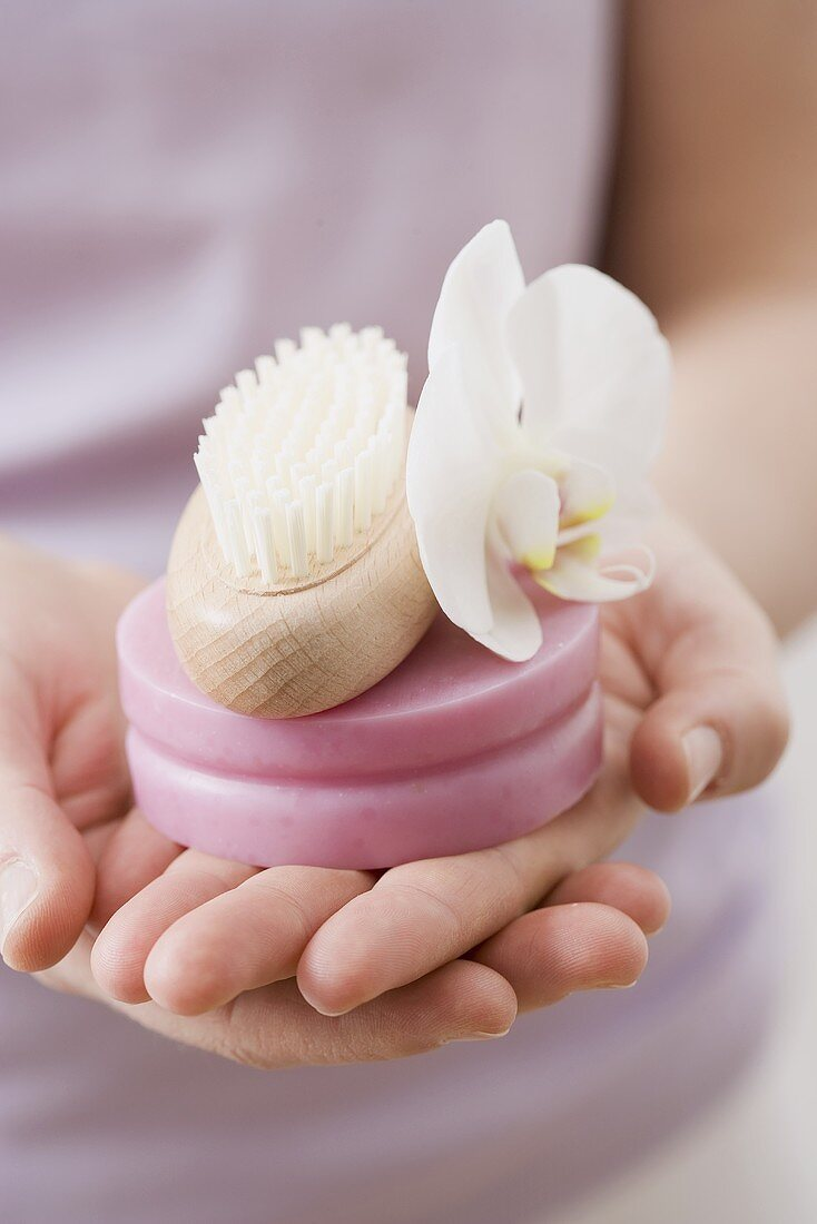 Woman holding soap, brush and orchid