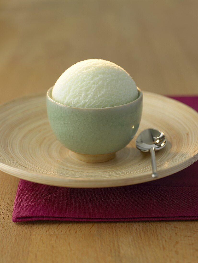A scoop of tea ice cream in a small green bowl