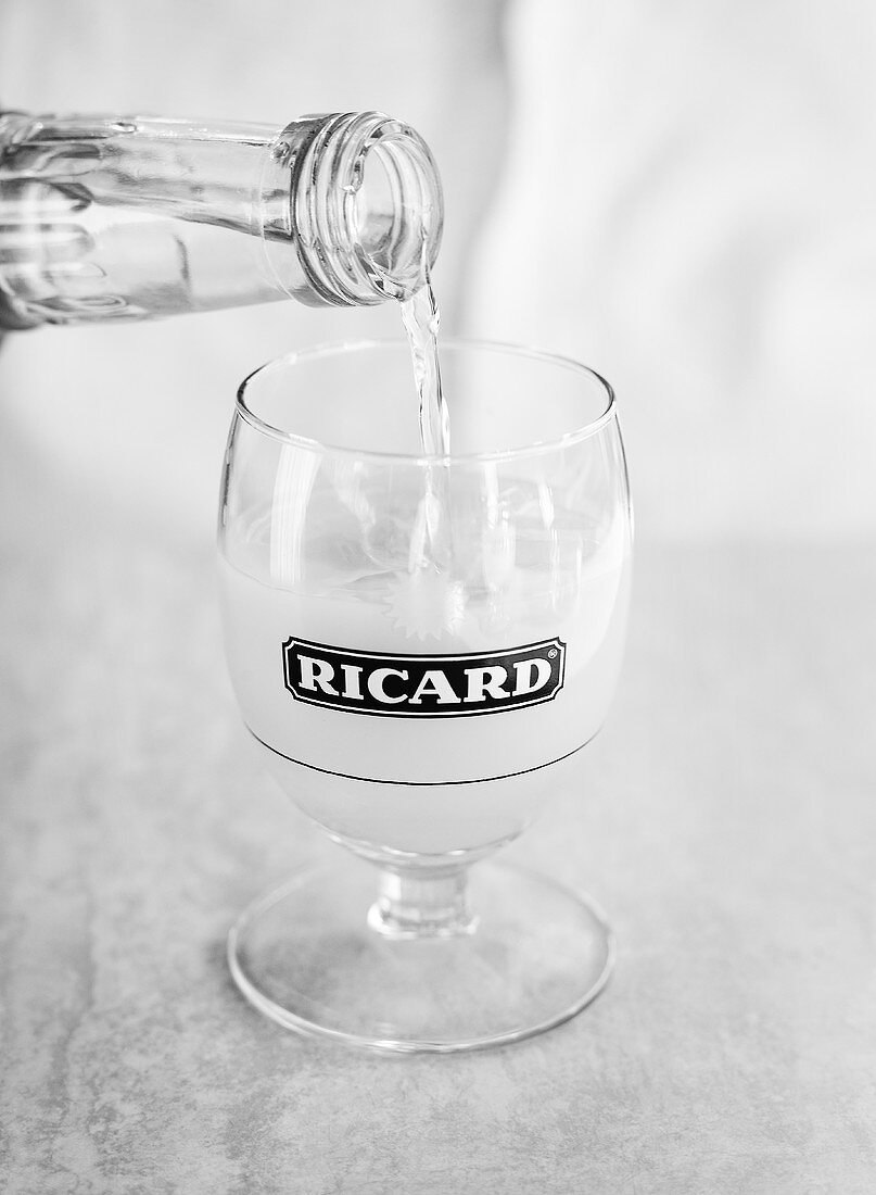 Pouring water into a glass of pastis