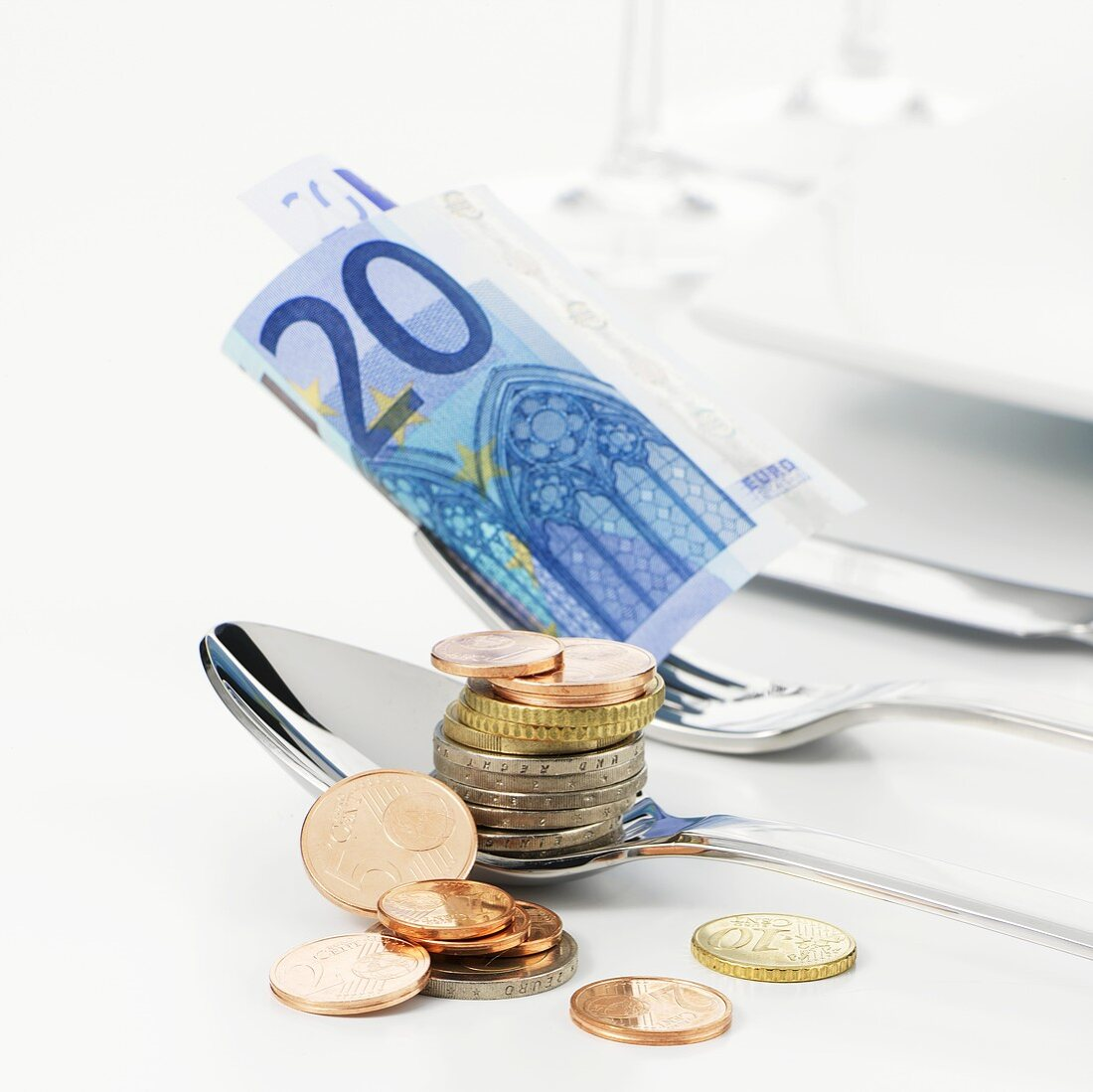 Euro coins on spoon, euro note on fork