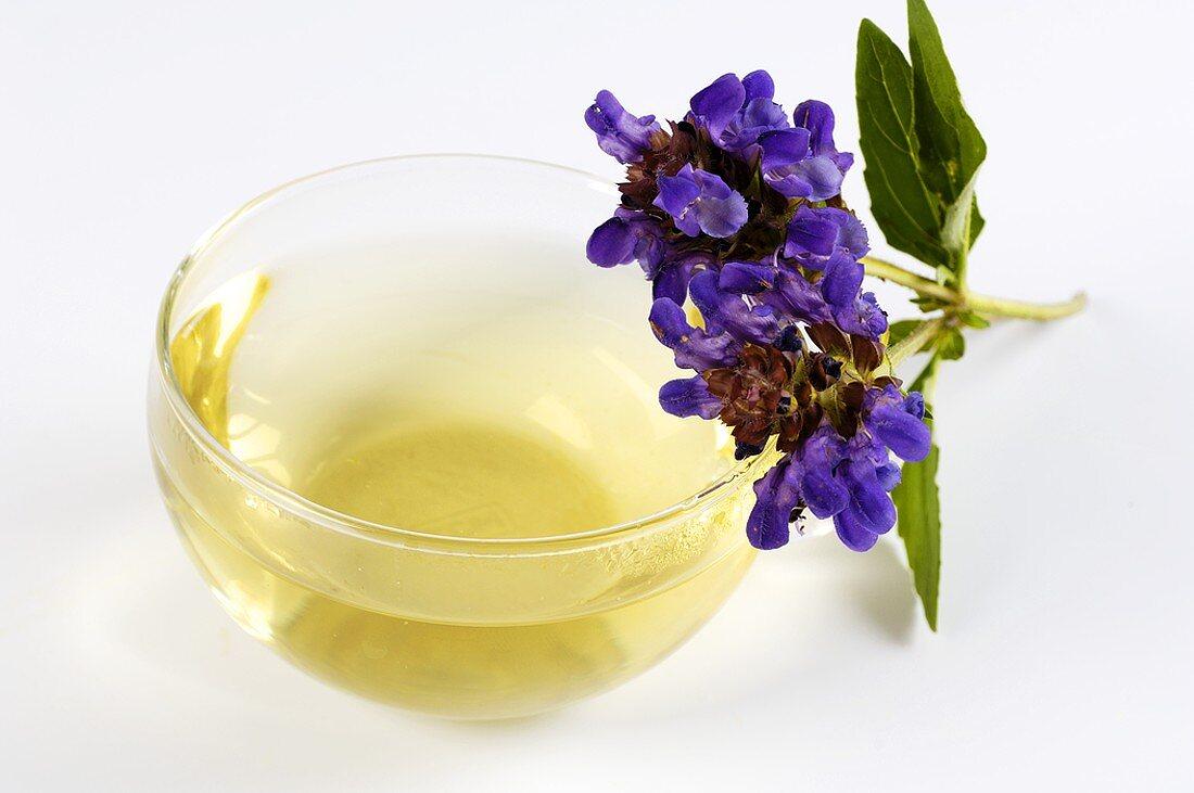 Cup of herbal tea, self-heal flowers beside it