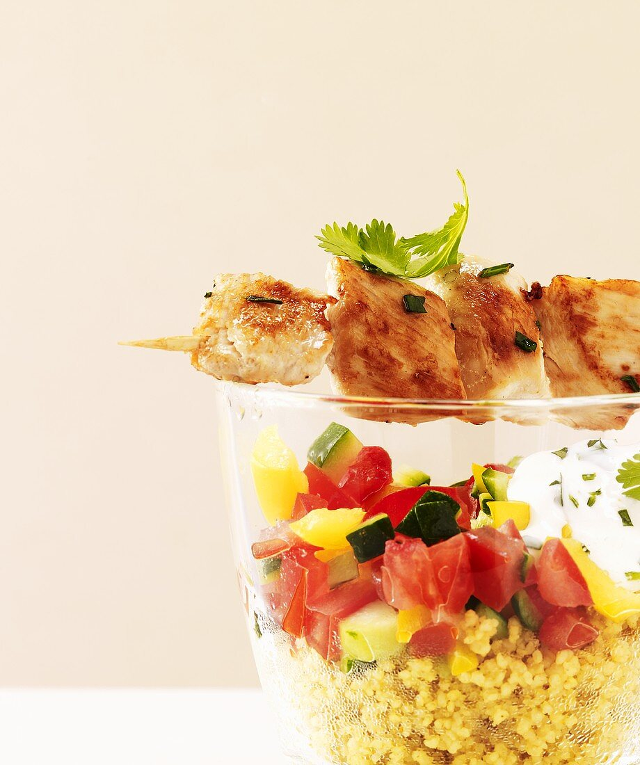 Chicken kebab over glass of couscous