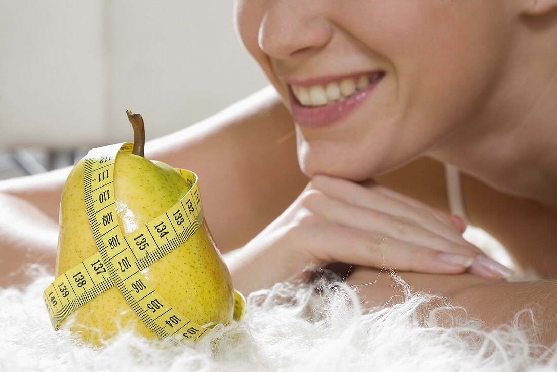 Pear with tape measure in front of young woman