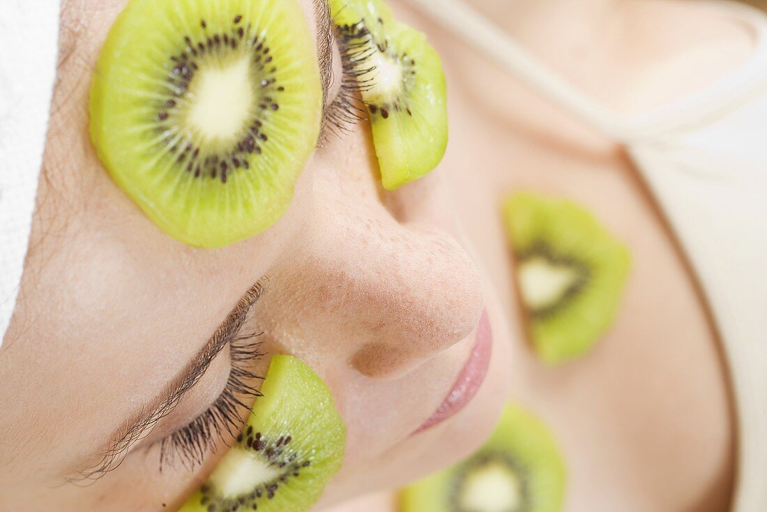 Young woman with slices of kiwi fruit on her face and neck