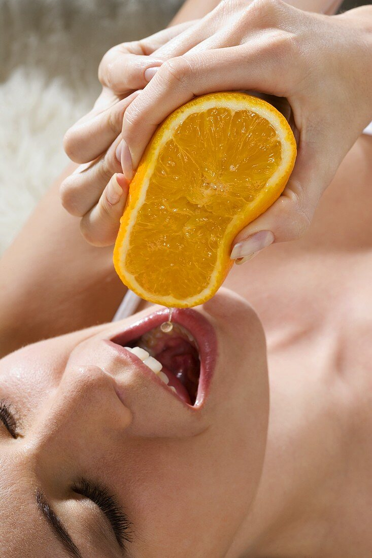 Young woman squeezing orange juice into her mouth