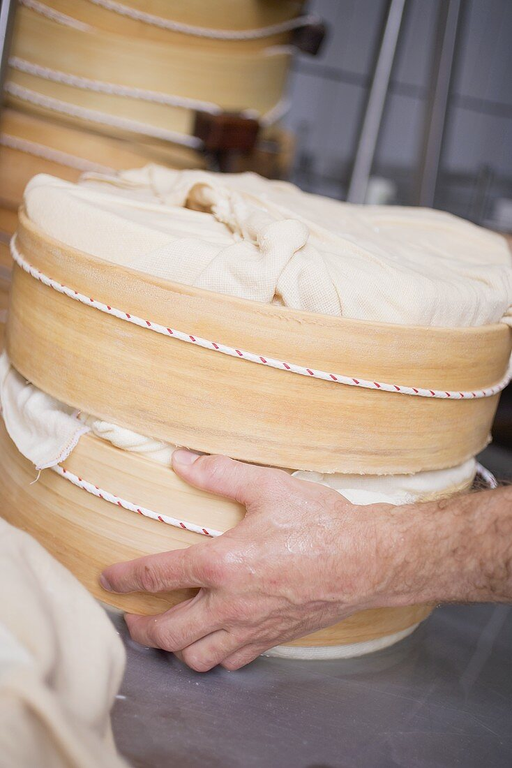 Hand holding wrapped cheeses in round wooden moulds