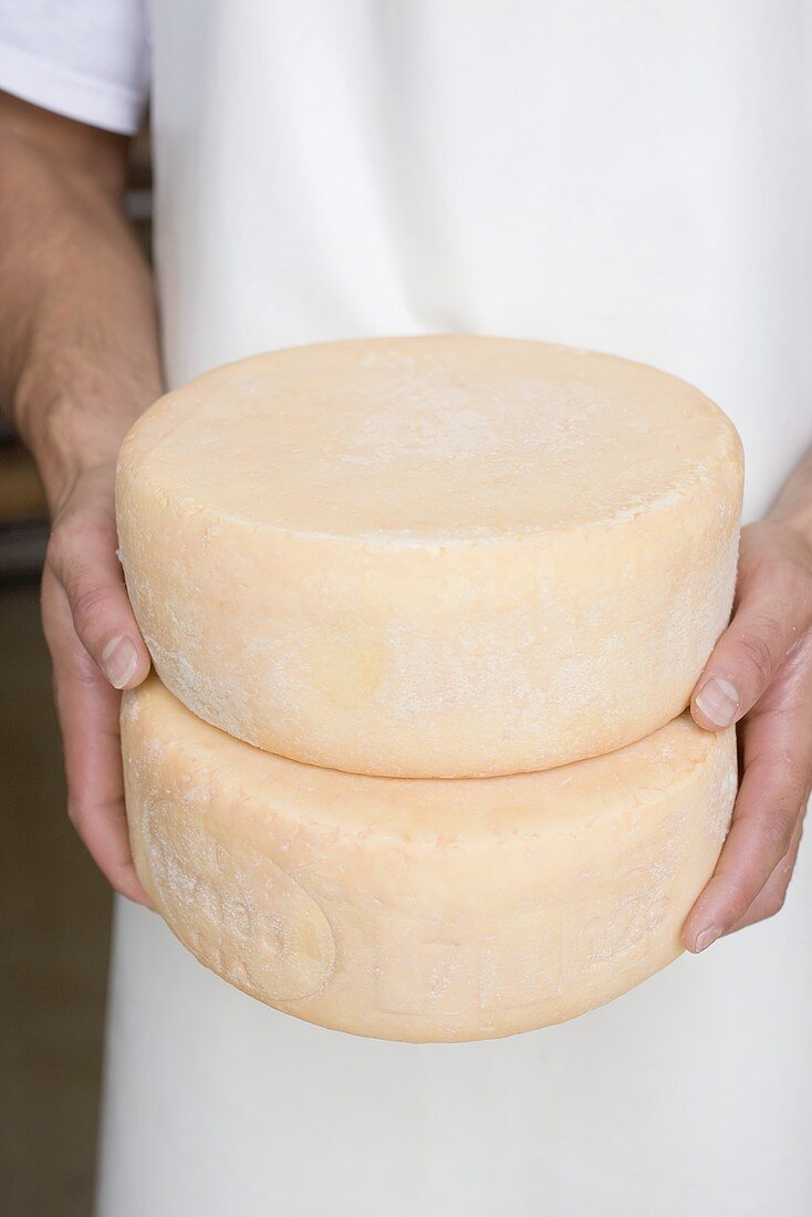 Man holding two round cheeses (Bauernkäse, farmhouse cheese)