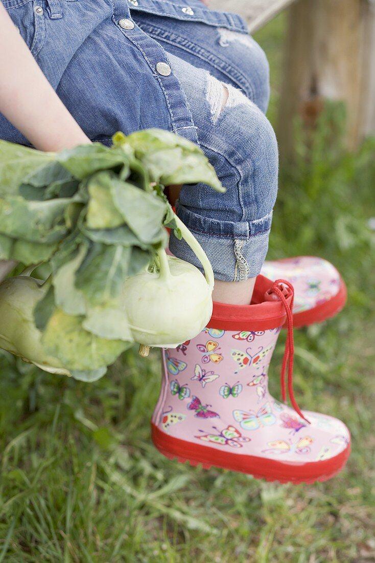 Child sitting on garden bench with freshly picked kohlrabi