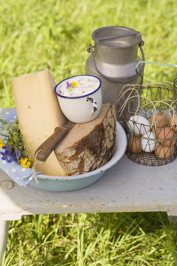 Rustic still life with bread, cheese, eggs and milk can