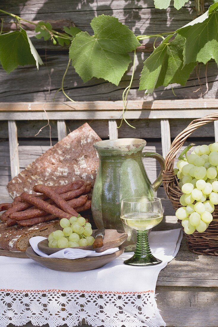 Grapes, bread, sausages & wine on wooden bench in front of farmhouse