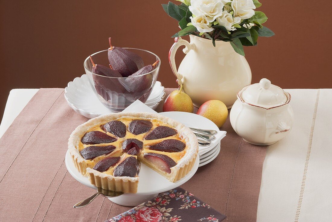 Red wine pear tart on cake stand, a piece cut