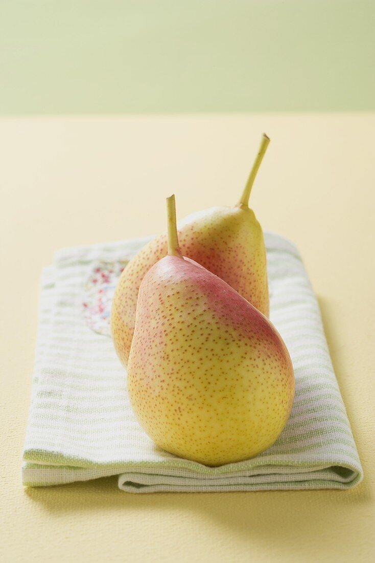 Two Forelle pears on a tea towel