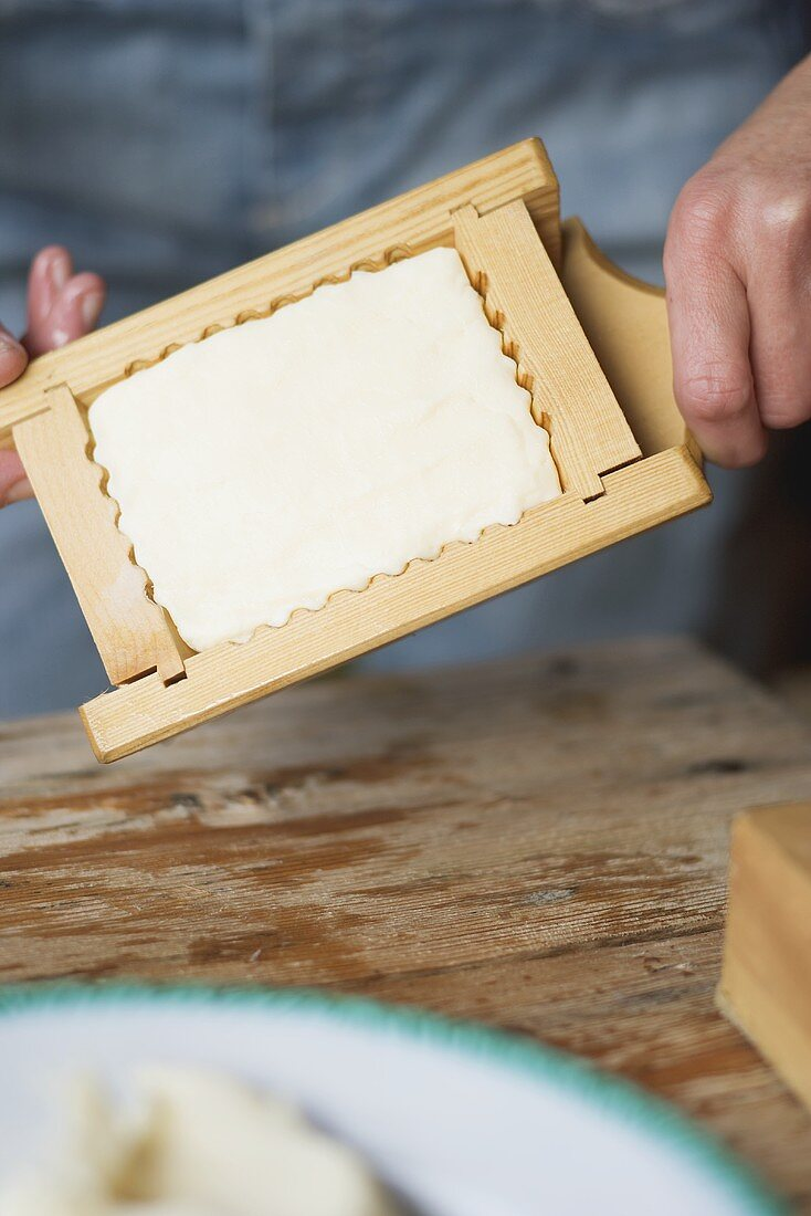 Hands holding farmhouse butter in a wooden mould