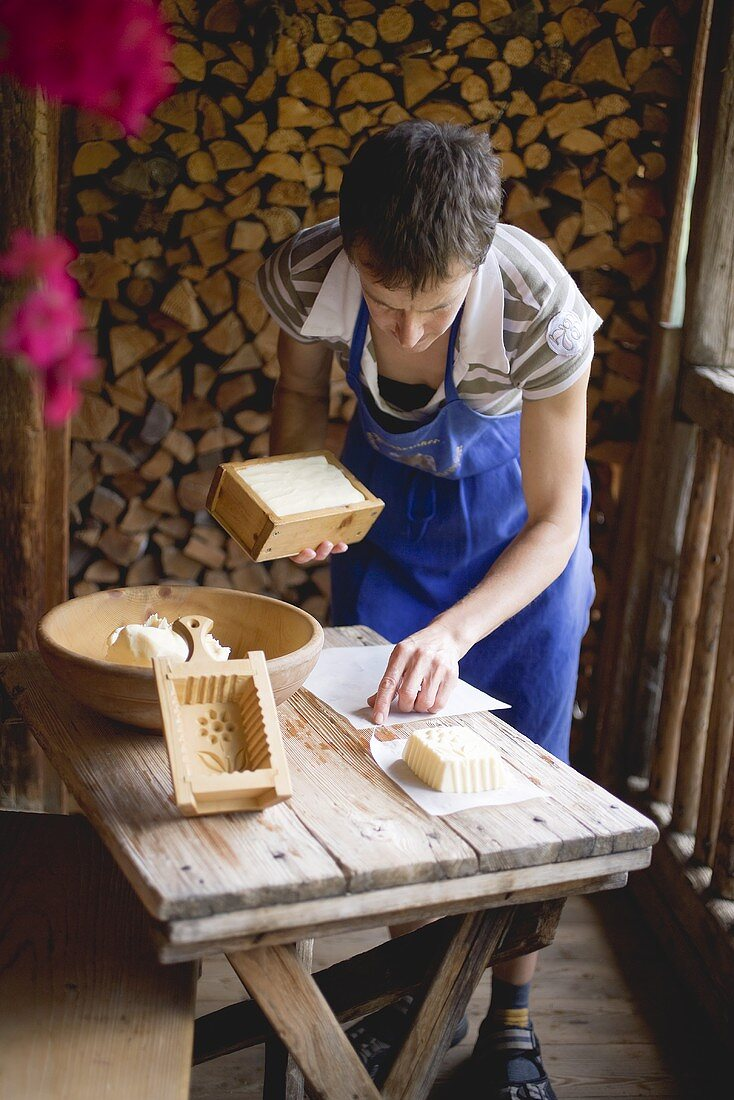 Woman with farmhouse butter & wooden moulds in Alpine chalet