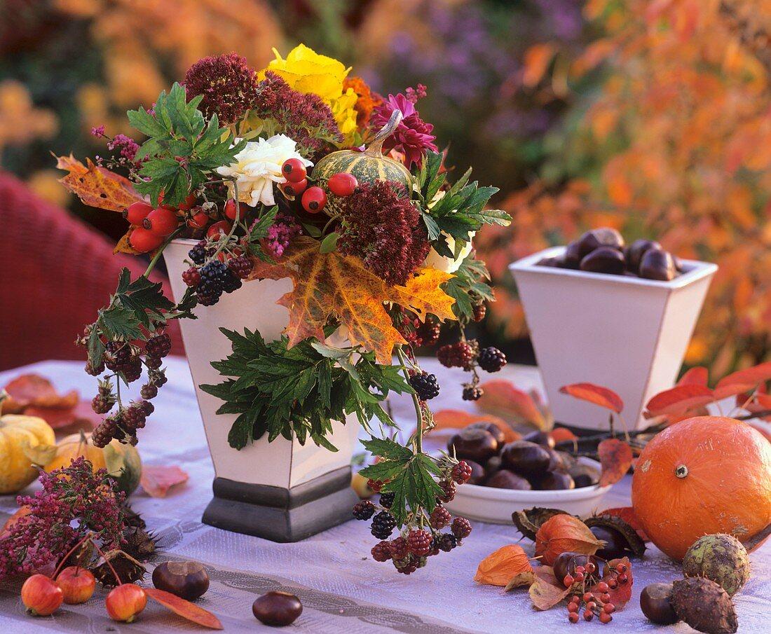 Autumn arrangement: maple leaves, rose hips & ornamental gourds