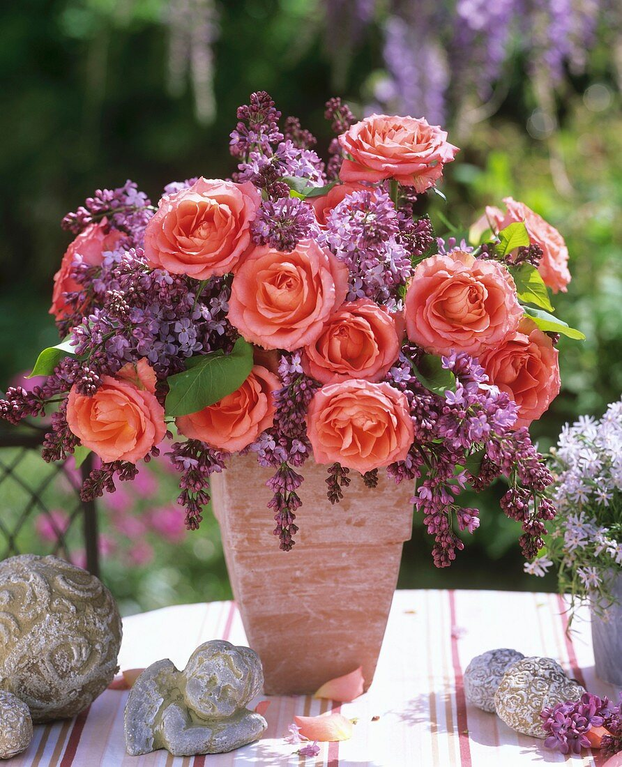 Arrangement of roses and lilac in terracotta vase, angel