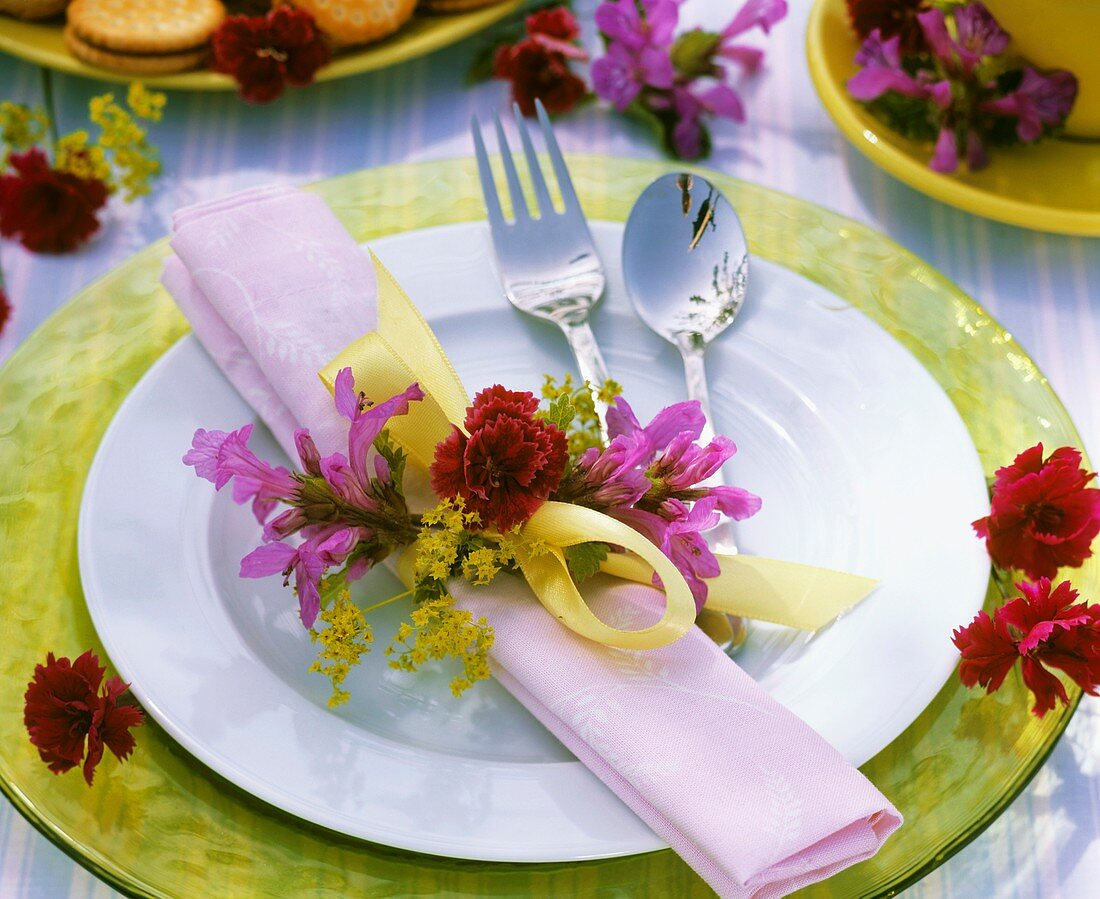 Place-setting decorated with Stachys, lady's mantle & carnation