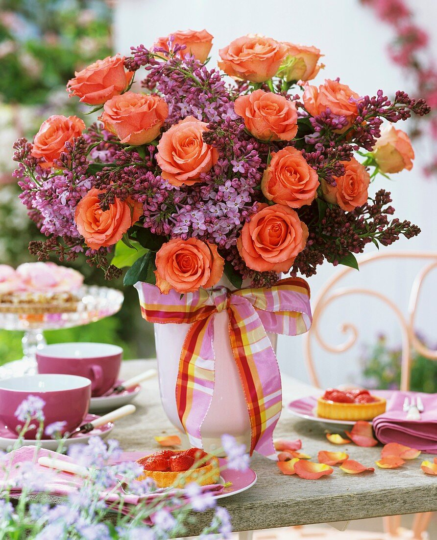 Arrangement of roses and lilac on table with strawberry tarts