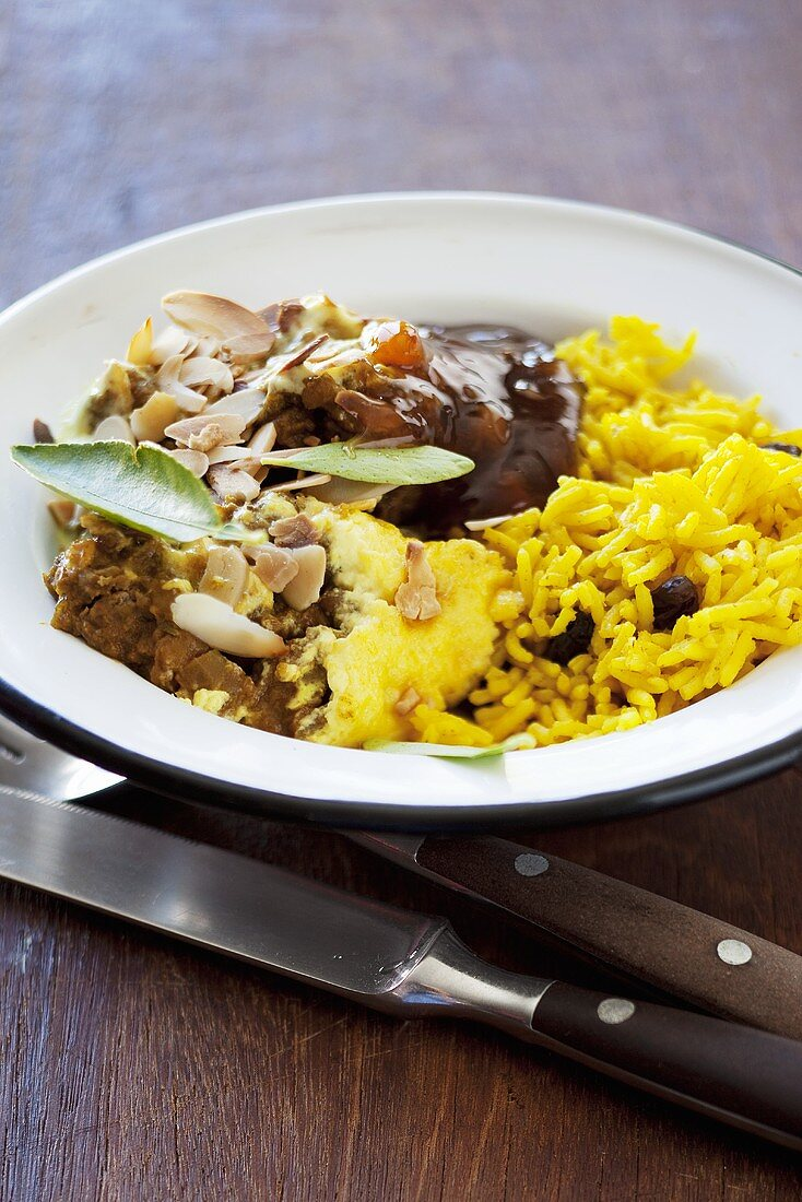 Bobotie (minced meat dish with a custard topping, South Africa) with chutney and saffron rice