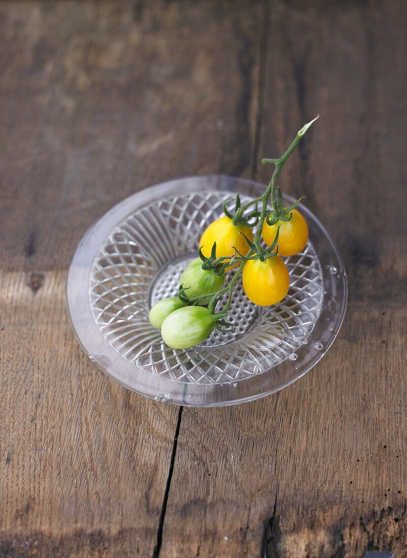 Ripe and unripe yellow plum tomatoes on glass plate