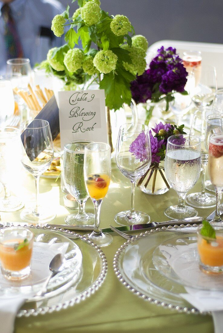 Table laid for special occasion with glasses of cold soup and aperitifs