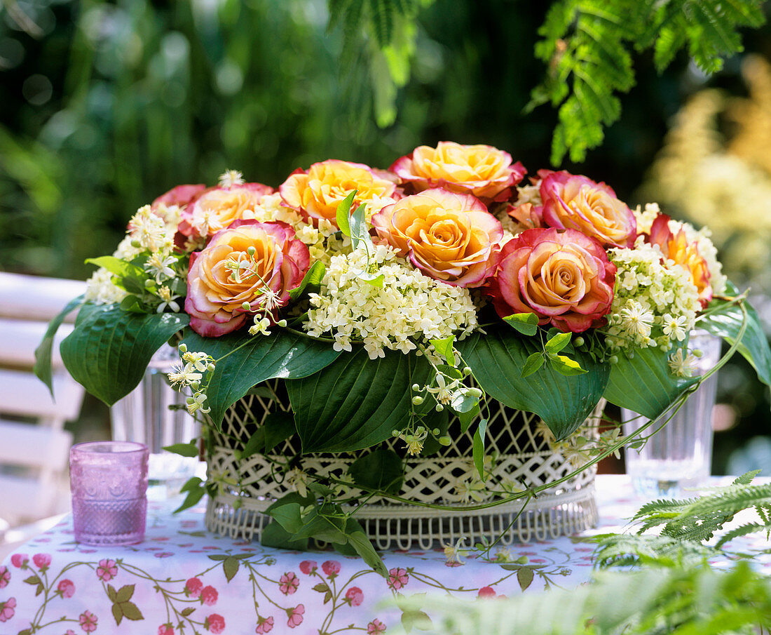 Wire basket with roses, hydrangeas, Clematis tendrils