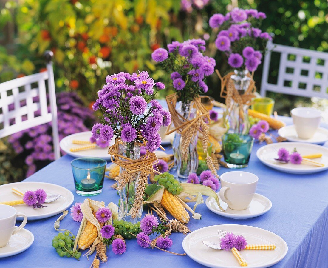 Laid table with Michaelmas daisies, sweetcorn and wheat