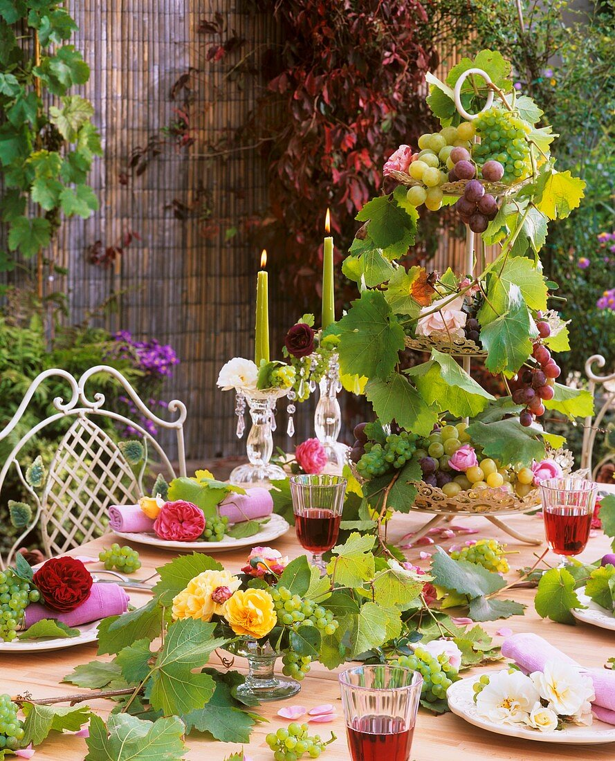 White, yellow, pink & red roses with grapes as table decoration