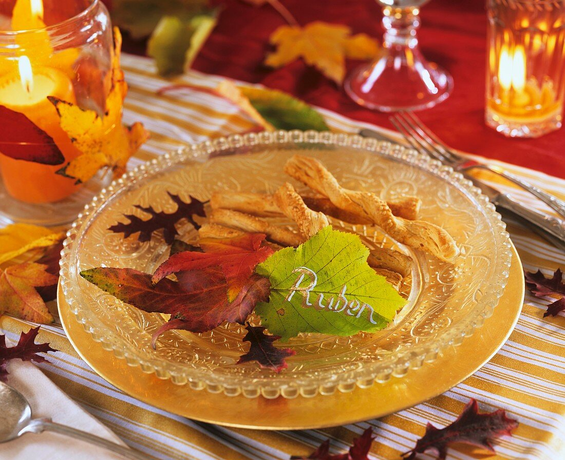 Savoury biscuits on glass plate, autumn leaves & leaf with name