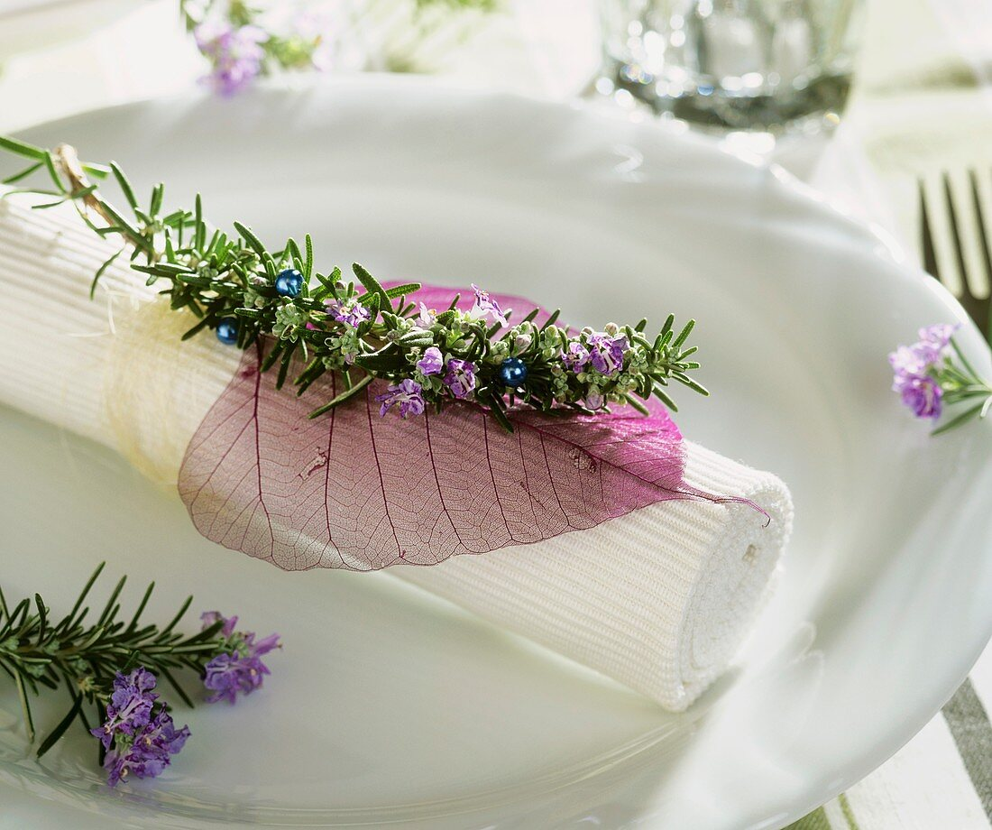 Napkin decoration with sprig of rosemary