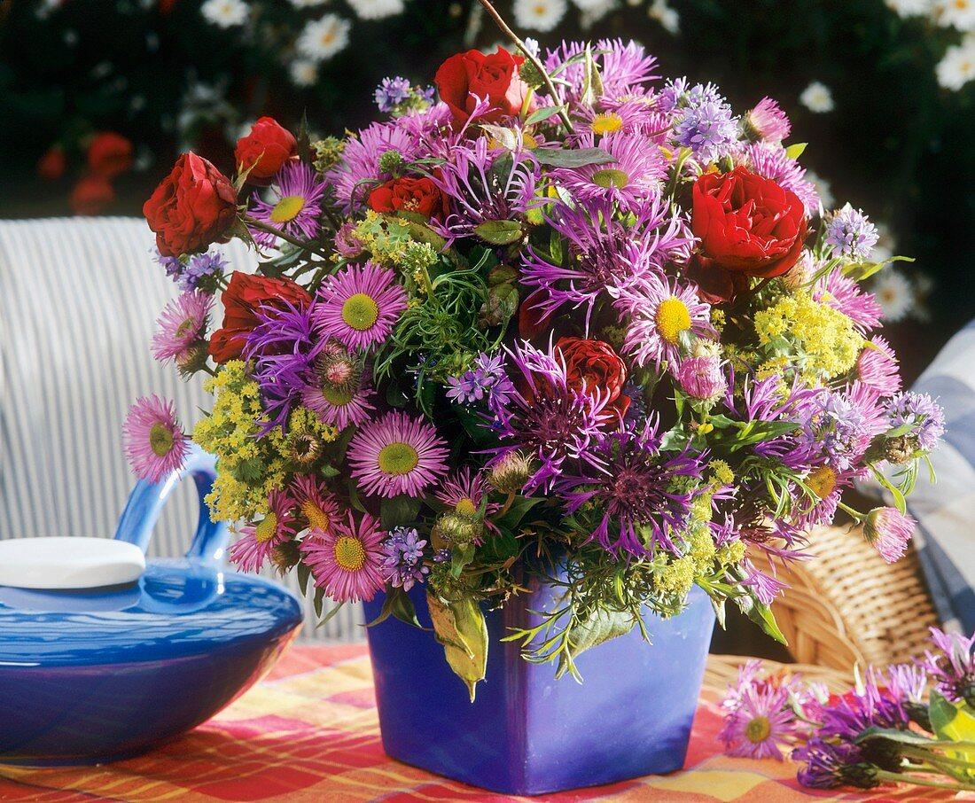 Arrangement of Michaelmas daisies, cornflowers and roses