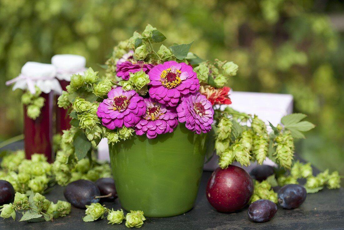 Vase of pompom dahlias and hops, plums, jam