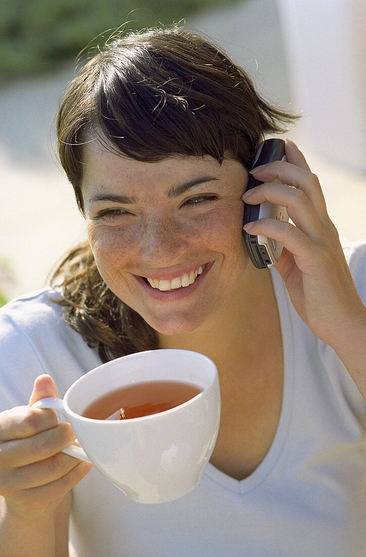 Young woman with a cup of tea and a mobile phone