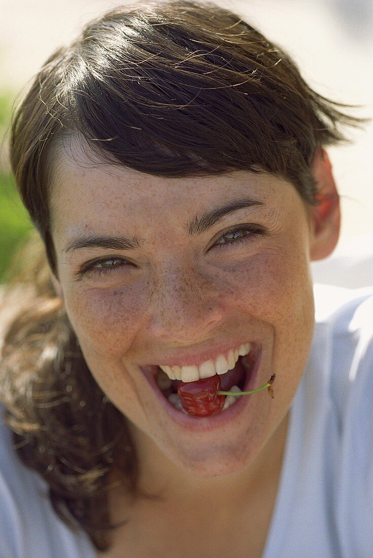 Young woman with a cherry in her mouth