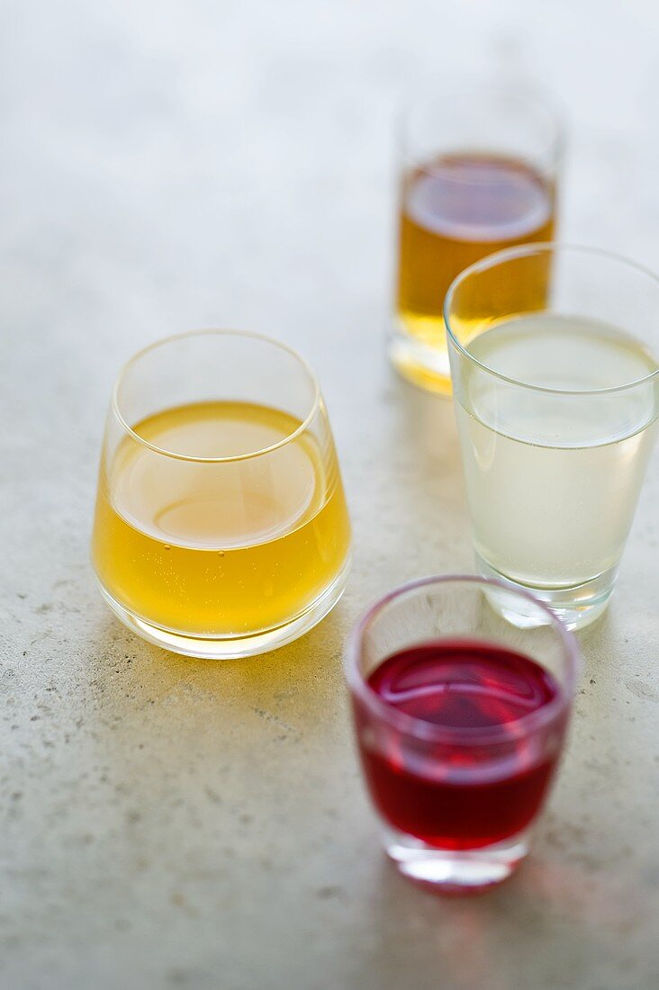 Different fruit liqueurs in four glasses