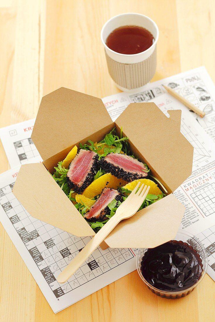 Rocket salad with fried tuna and orange segments in a take-away box
