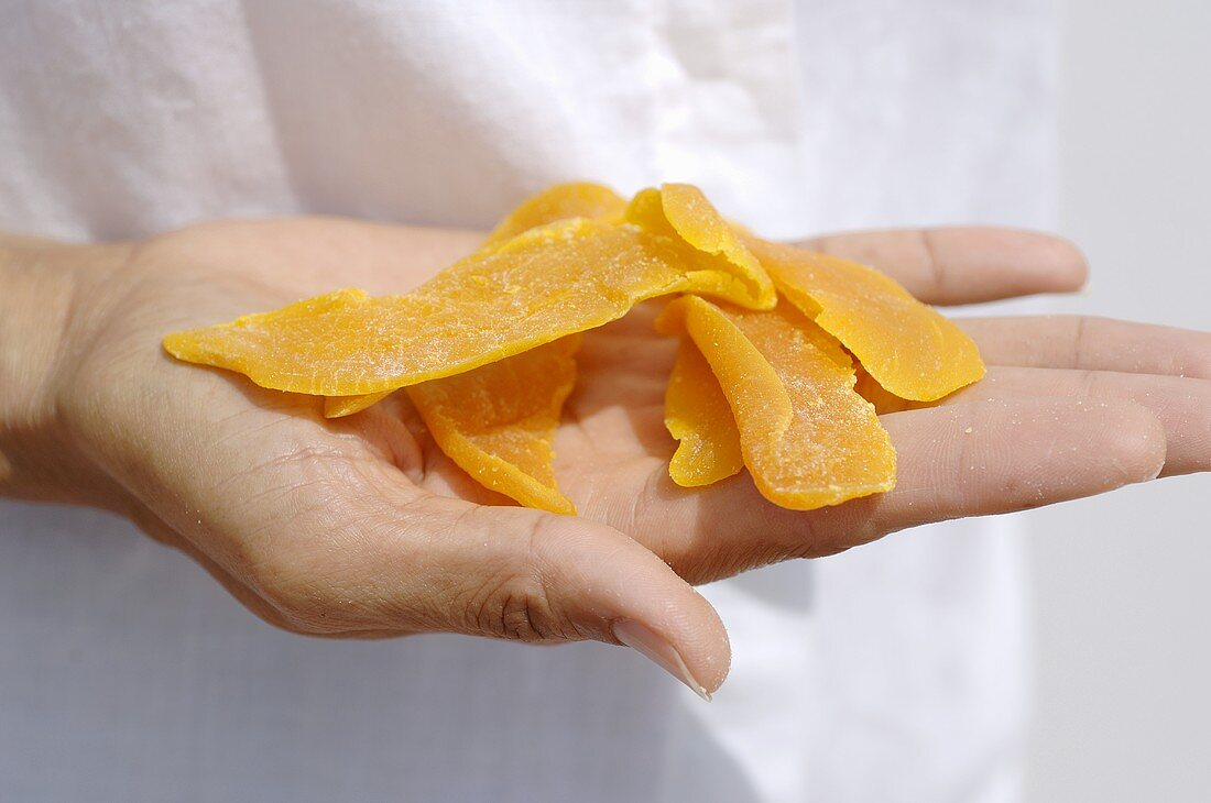 Hand holding dried mango slices
