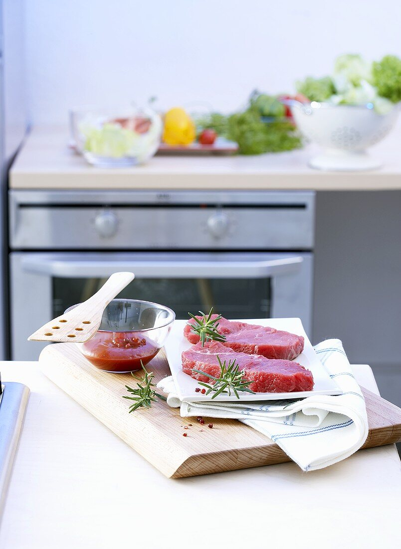 Beef steaks with ingredients on a kitchen table