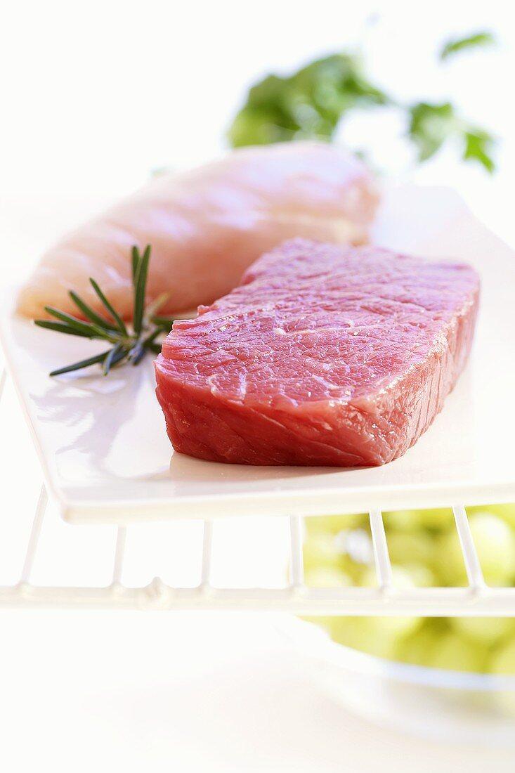 Beef steak and chicken breast fillet in refrigerator