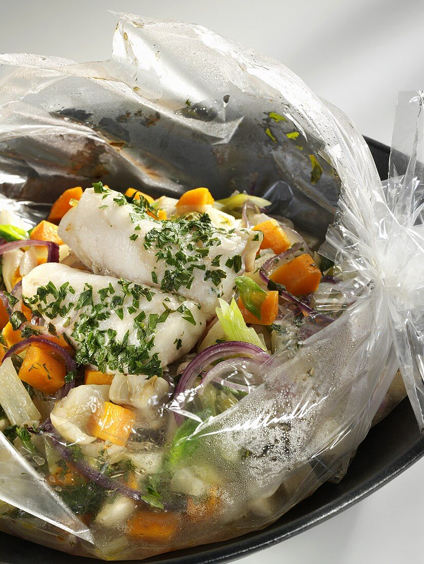 Coley with herbs and vegetables cooked in roasting bag