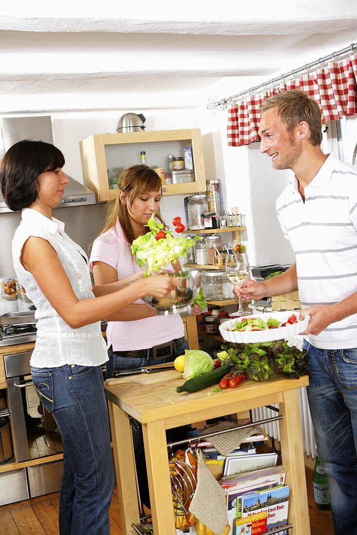 Three young people preparing salad together