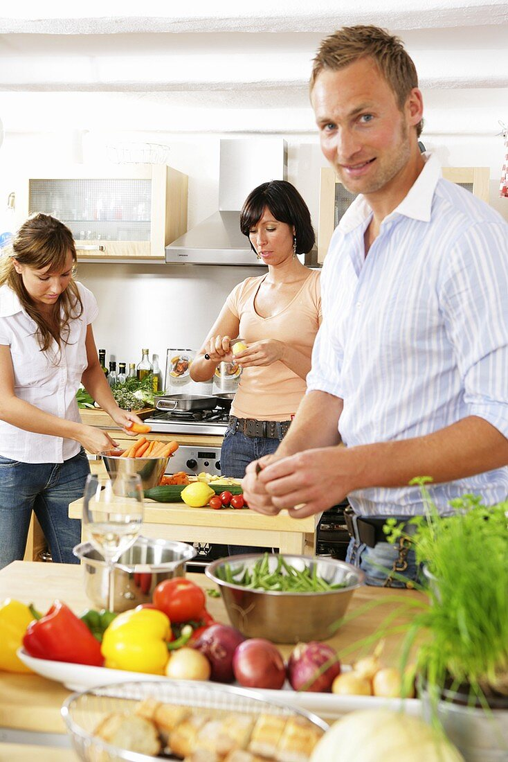 Three young people preparing vegetables in kitchen