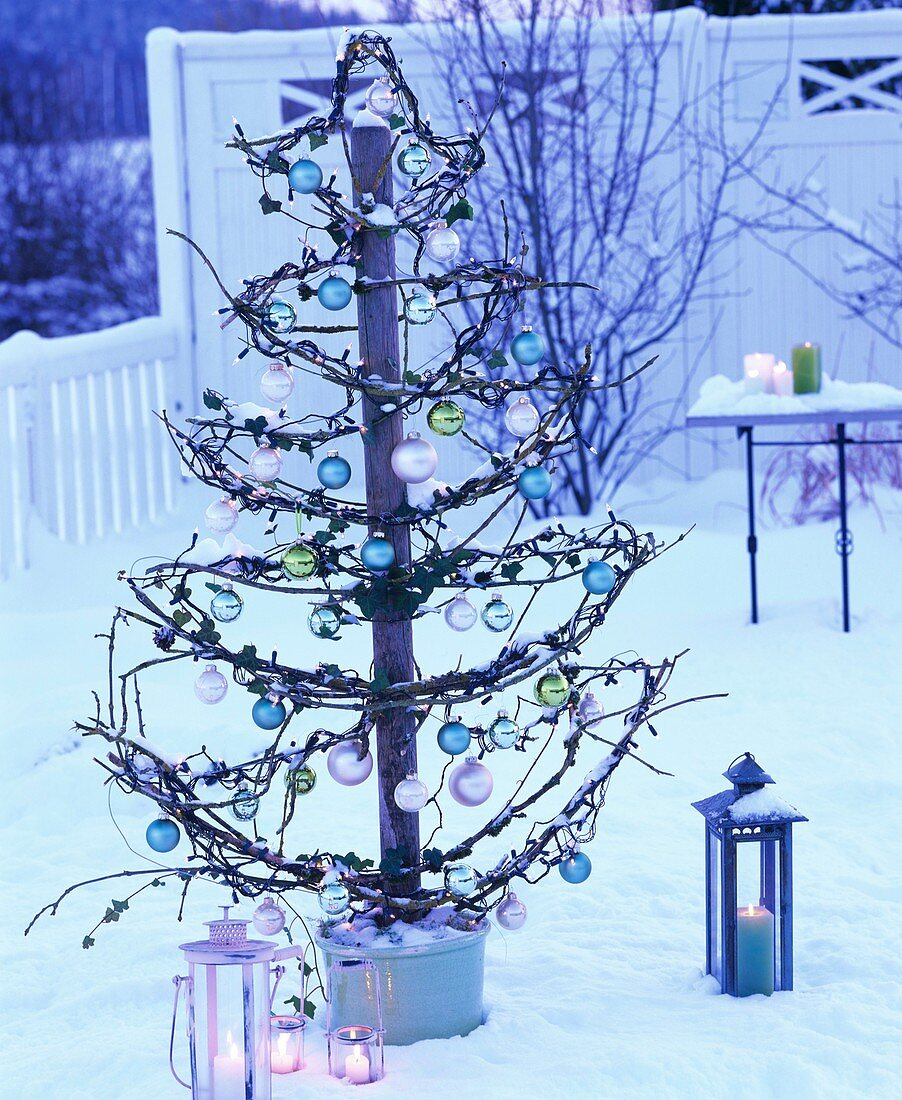 Skeleton Christmas tree with glass baubles & fairy lights outside